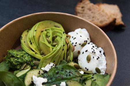 A beautiful dish: sliced avocado, poached eggs and pumpkin seeds. Close-up Stok Fotoğraf
