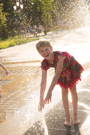 Happy girl in the spray of the fountain. The child smiles in the rays of the sun. Summer heat