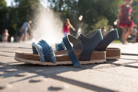 In the foreground are children's orthopedic sandals. Blurred image in the background. Children having fun in the fountain. The jets of the fountain allow you to cool off in hot summers. Sunshine, fun and bright colors.