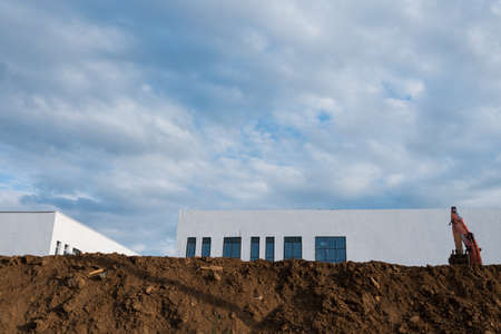 Construction site. Lots of dirt, an excavator and a new white building. Blue sky with clouds