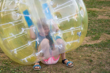 A child in a bumperball. Legs in shorts are visible from an inflatable ball. Fun on the summer lawn