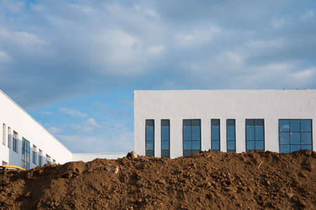 Construction site. Lots of dirt and a new white building. Blue sky with clouds Stok Fotoğraf