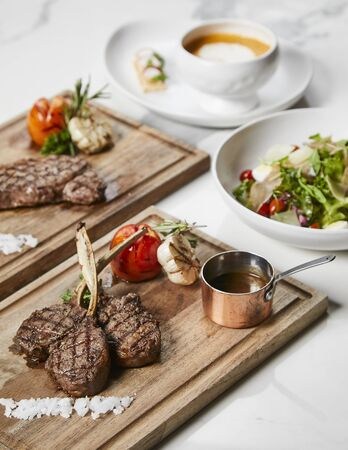 Lamb rib chops steak served with roasted vegetables and gravy sauce on cutting board, white marble background