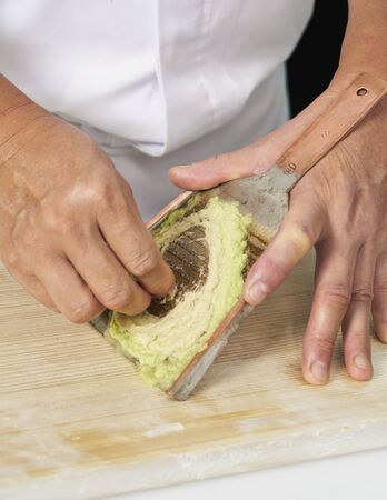 Wasabi stems grated to paste form by chef, Wasabi on a metal oroshigane grater Foto de archivo