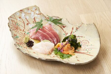 Premium Sashimi garnished with edible flowers in ceramic plate on wooden background