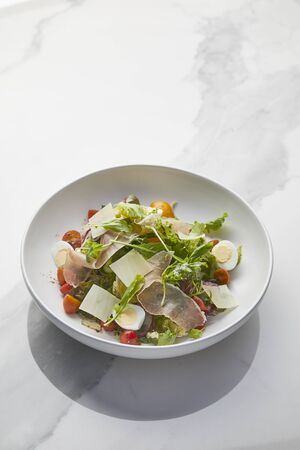 Garden salad with parma ham in white plate on white marble background