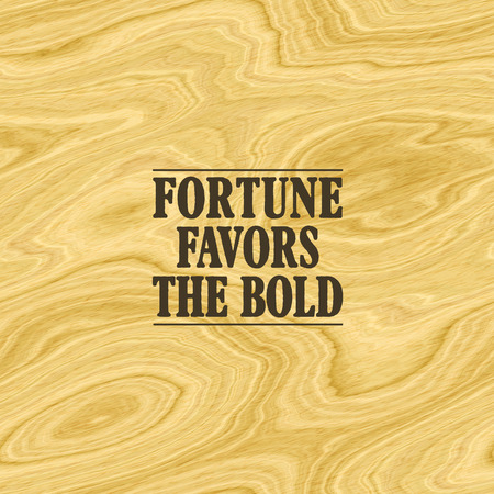 audacious: One of the most famous inspirational quotes  sayings, Fortune Favors the Bold, pictured on a light brown wood background. Stock Photo