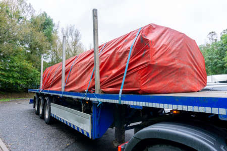 Semi Truck Blue Trailer with a Red Tarpaulin Weather Protecting a Load of Steel Covering the Cargo of Steel and Strapped up with Blue Ratchet Straps and Metal Side Posts inserted into the Flatbed.