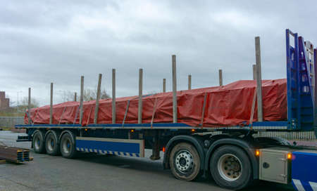Flat Bed Trailer Carrying Steel Covered with a Red Tarp and Secured Cargo with Ratchet Straps, outdoors on a Overcast Day.