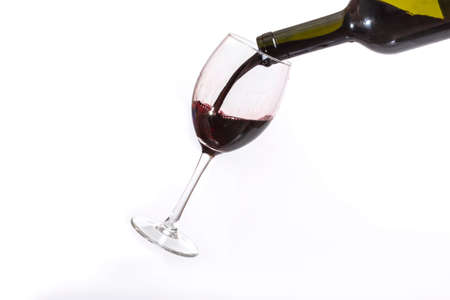 red wine pouring: Red wine pouring in a wineglass on a white background