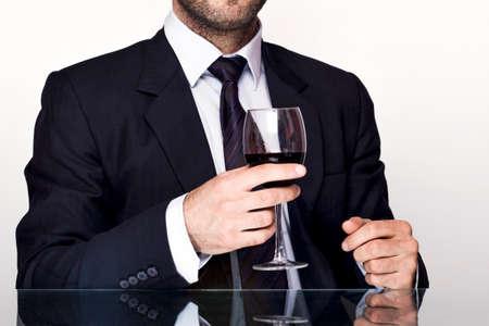 jovenes tomando alcohol: Empresario sosteniendo un vaso de vino tinto