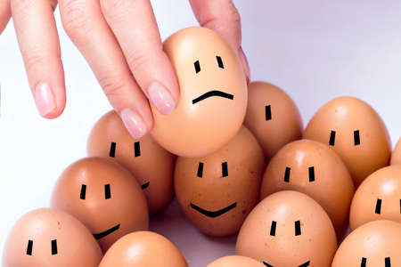 faces happy to sad: Selected egg feeling sad from other ones Stock Photo