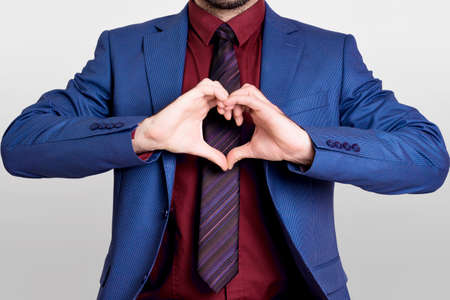 grabing: Businessman in red shirt showing a heart shape