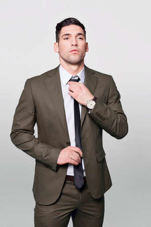 grabing: Handsome man in grey suit adjusting his tie