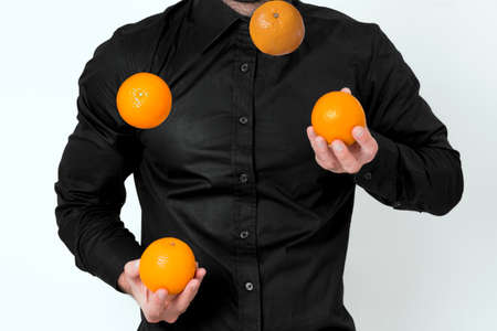 Man in black shirt juggling with oranges Stock Photo