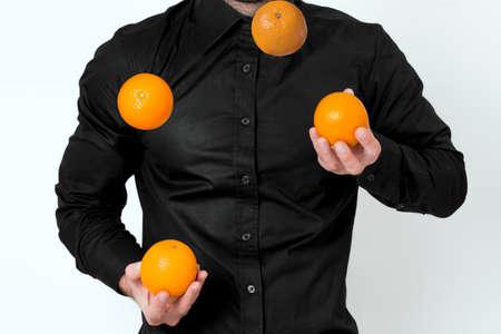 juggling: Man in black shirt juggling with oranges Stock Photo