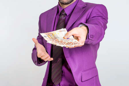 giving money: Businessman in purple suit giving money euros Stock Photo