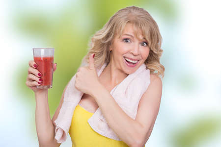 gorgeous woman: Woman showing a glass of a fruit red smoothie Stock Photo
