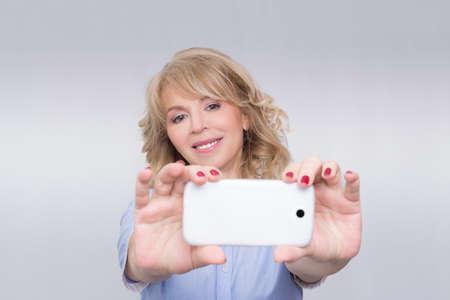 femme blonde: Femme prenant une photo avec son t�l�phone portable