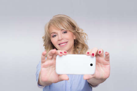 Woman taking a photo with her cell phone Stock Photo