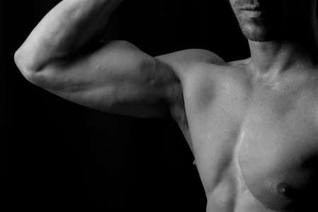 strong men: Man flexing biceps in black and white