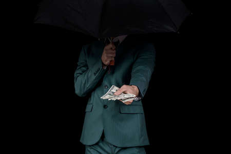 Gangster offering money behind umbrella Stock Photo