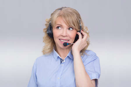 older woman smiling: Blonde woman operating in call center