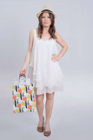 bra model: Beautiful brunette woman in a white dress after shopping Stock Photo