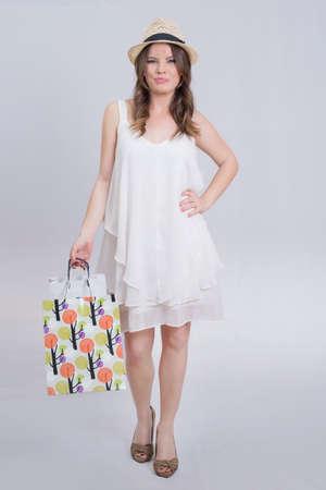 poses de modelos: Hermosa mujer morena con un vestido blanco despu�s de las compras
