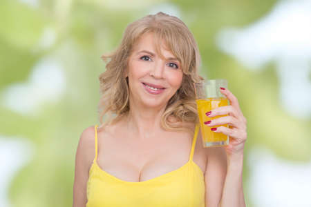 woman in water: Blonde woman holding a glass of orange juice Stock Photo