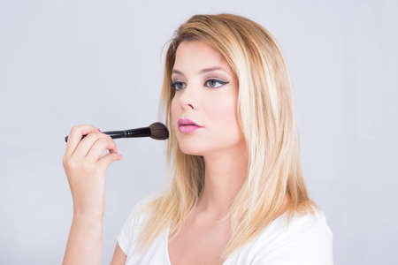 eye care professional: Beautiful blonde woman putting on makeup