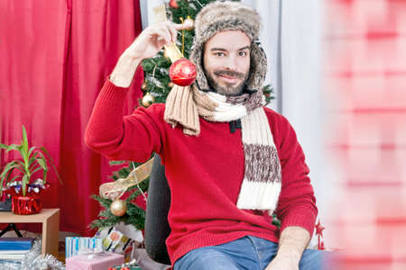 gold christmas decorations: Man holding a christmas ornament Stock Photo