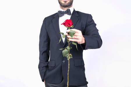 Man in suit holding a rose for Valentines