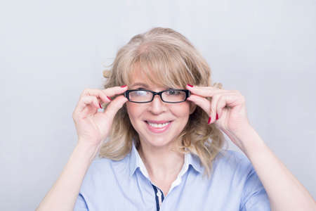 older woman smiling: Businesswoman holding her glasses
