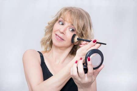 femme blonde: Elder femme blonde souriante et mise sur le maquillage