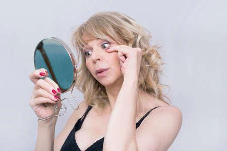 femme blonde: Mi v�rifier ses rides dans le miroir femme �g�e