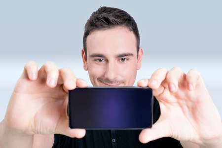 photo shooting: Man taking a selfie on his cell phone