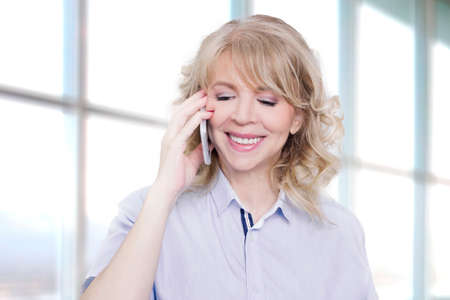 woman with phone: Blonde woman speaking on her cell phone indoors Stock Photo