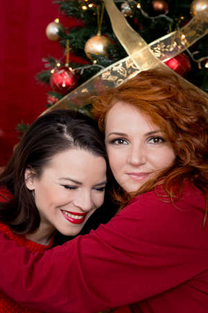 young girl models: Two girls hugging for Christmas