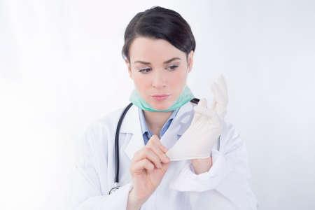 surgical mask woman: Female doctor adjusting rubber gloves