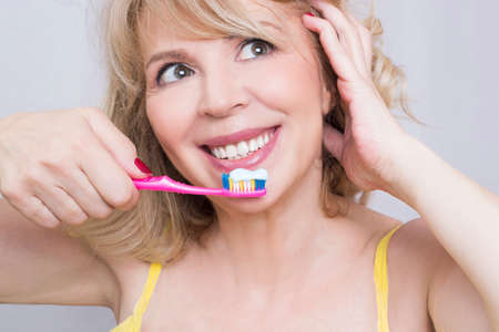 older woman smiling: Blonde woman brushing her teeth smiling