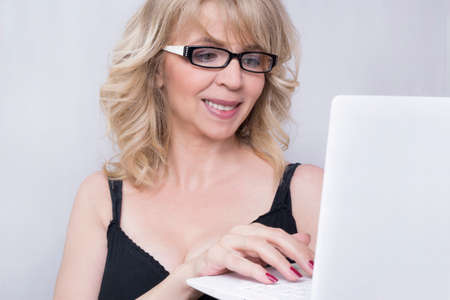 older woman smiling: Business woman typing on lap top Stock Photo