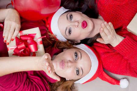 mooie vrouwen: Twee meisjes blazende kussen voor Kerstmis