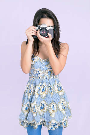 pastel flowers: Hipster woman taking a photo with a vintage camera