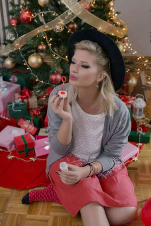 woman blowing: Blonde hipster woman blowing bubbles for Christmas