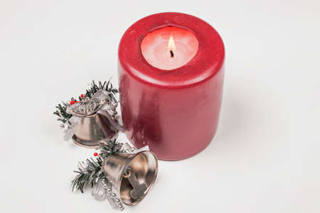 silver bells: Red candle and two silver bells for Christmas Stock Photo