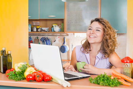 lap top: Happy woman in kitchen with a lap top Stock Photo