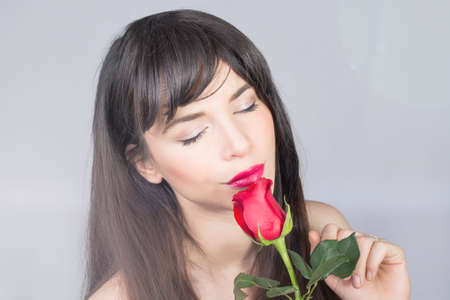 red and blue: Beautiful girl smelling a red rose