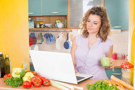 lap top: Happy housewife with a lap top in a kitchen