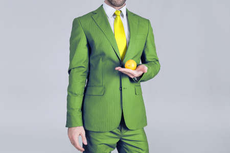 Healthy man in green suit holding a lemon